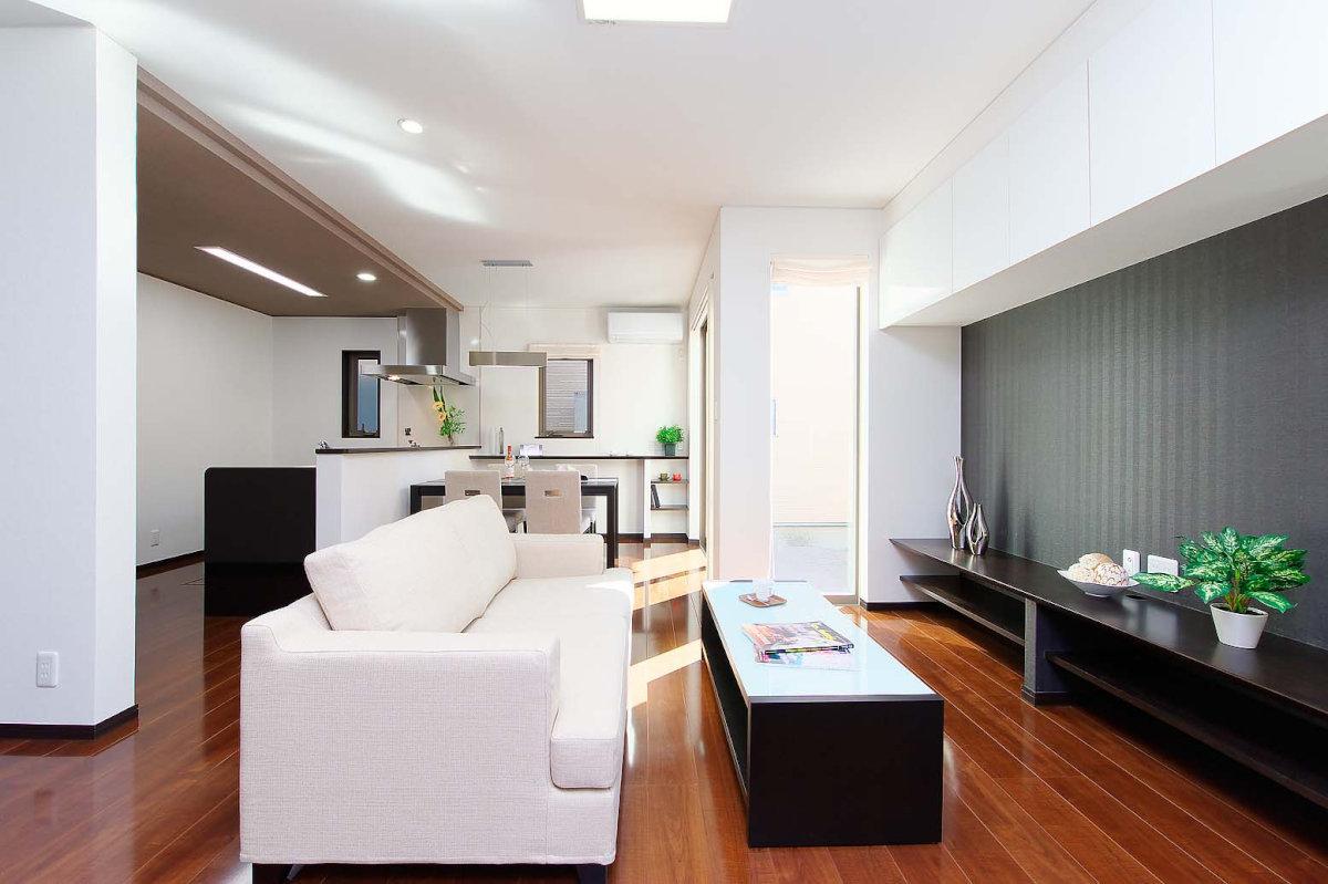 living(リビング) 玄関ホールの扉を開くと、視界に広がるのはホワイトとブラウンのバランスが絶妙なワンルームのLDK。隣接したテラスからたっぷりと注がれる自然光が、心地よい住空間をつくりだします。  インテリア性の高い作りつけの棚は大型テレビを愉しむテレビカウンターとして、またグリーンやお気に入りの雑貨をディスプレイするスペースとしてリビング空間に彩りを添えます