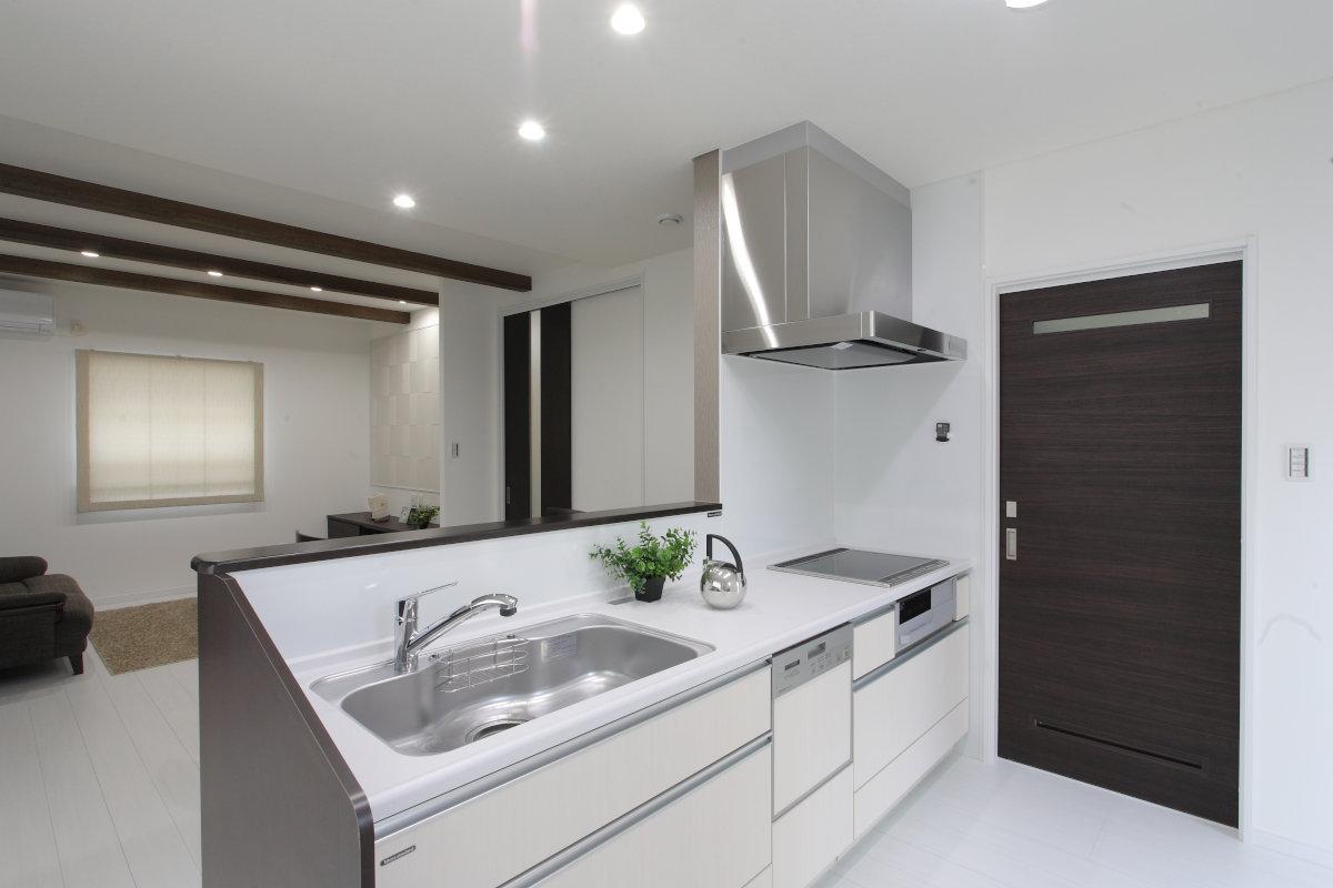 kitutin(キッチン) 床や壁の色に統一した白いキッチン。ダウンライトでまとめているので天井がスッキリとみえます。奥の扉を開けると、すぐに脱衣室があり奥様に嬉しい家事動線となっています。