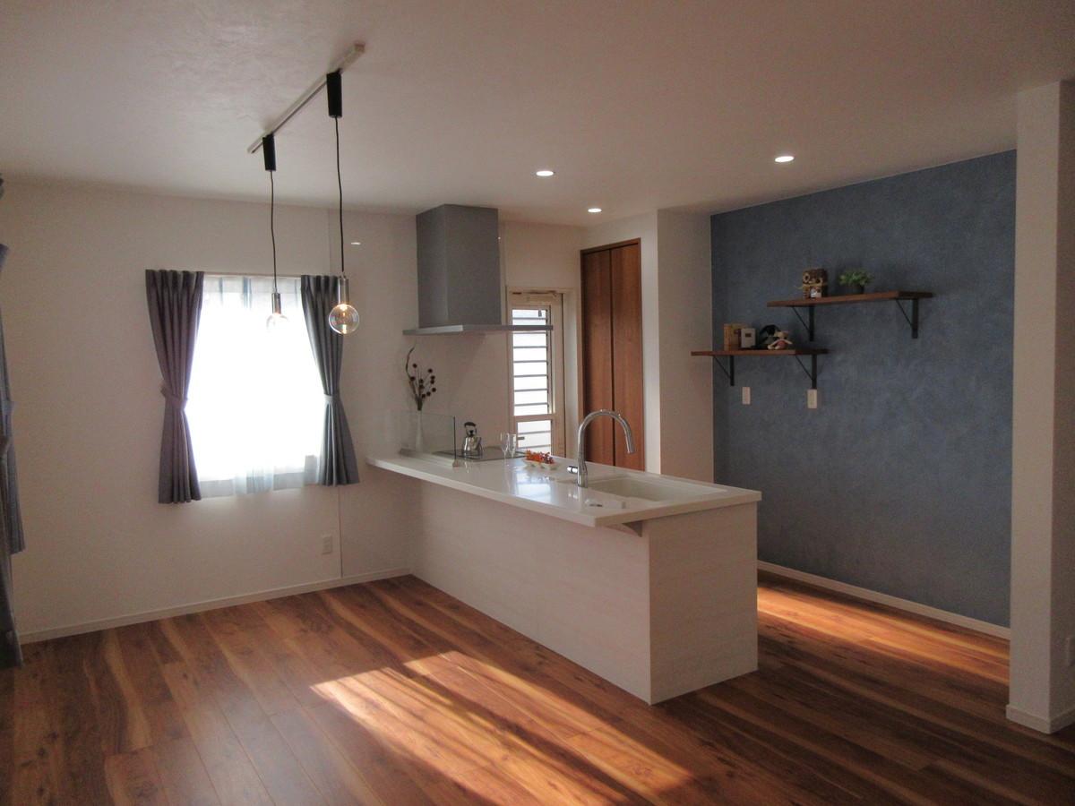 LDKと一体感のあるキッチンが、より広い空間を感じさせます。 キッチン背面のブルーの塗装に造り棚がアクセント。
